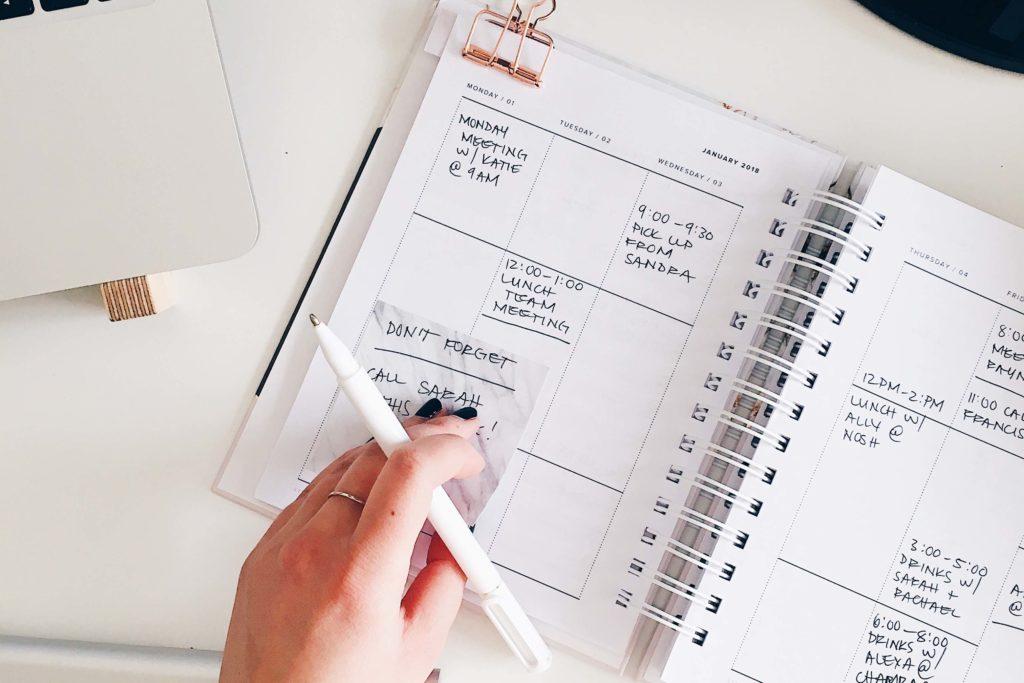 Se ve una agenda abierta con la mano de una mujer sujetando un bolígrafo